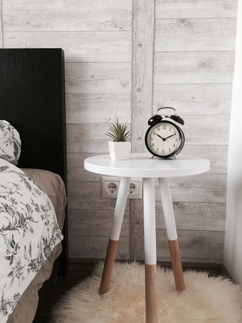 night stand next to bed with clock