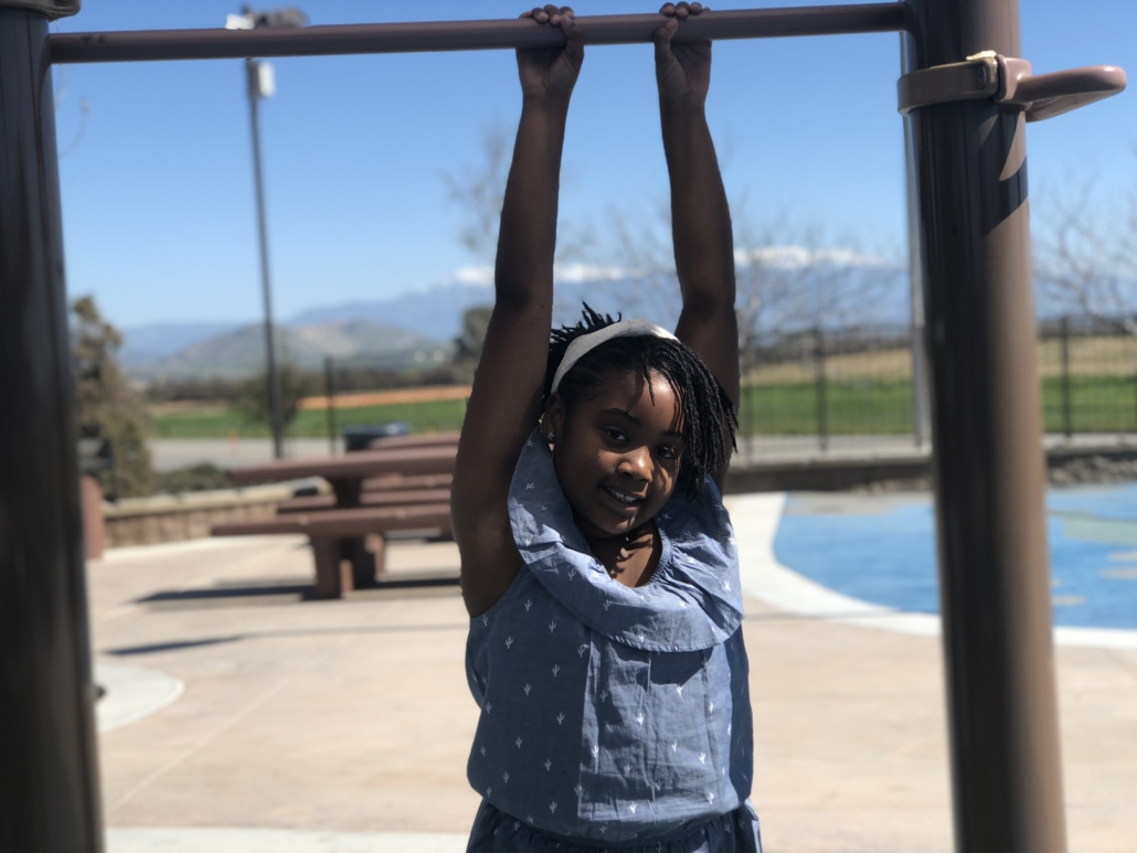 Aniyah hanging from monkey bars in a blue dress
