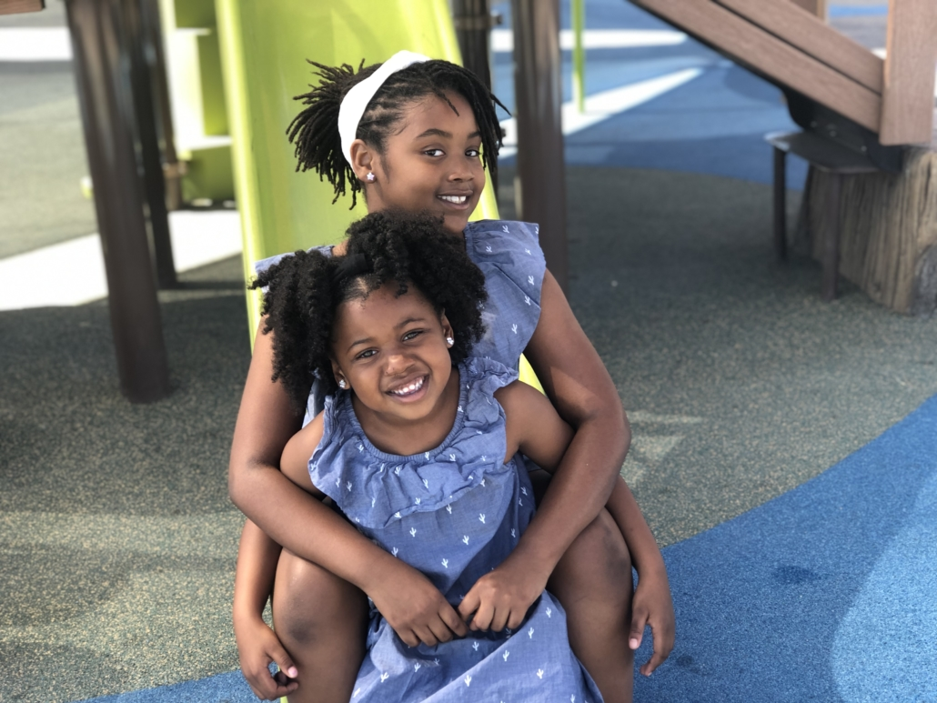 two black Brown skinned girls sitting on a slide with natural hair