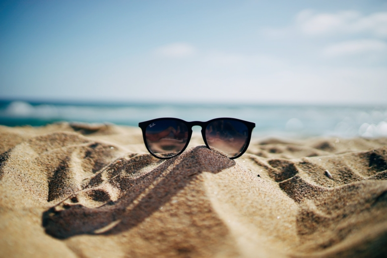 glasses on a mound of sand on the beach