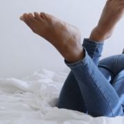 Woman laying on bed with legs crossed